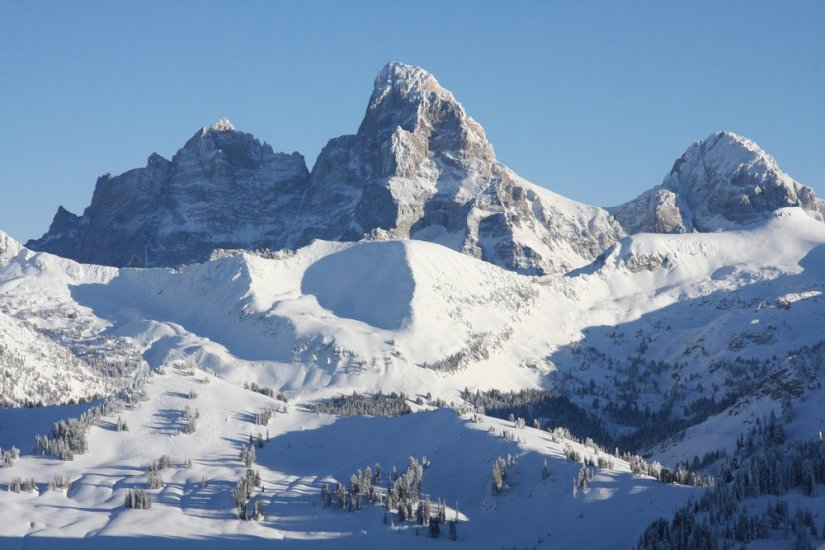 A classic view of Grand Teton National Park in winter: peaks covered in snow with blue skies