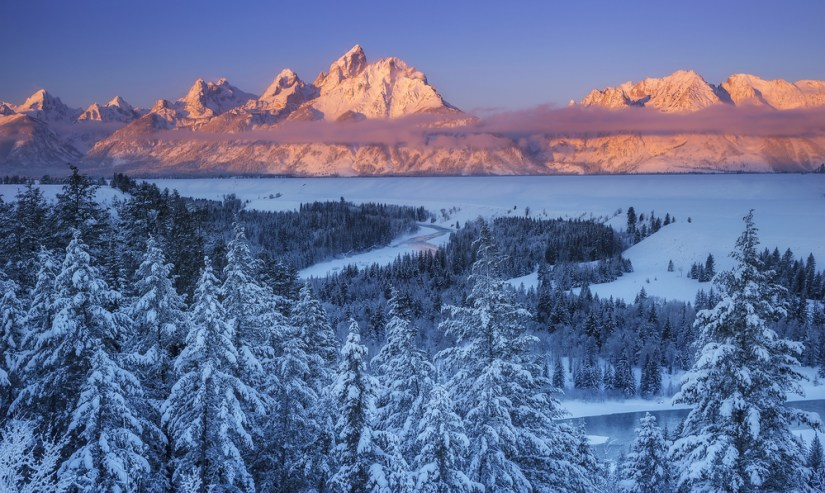View of the Grand Tetons at sunset with sun colors lighting up the mountains in pastel pink and lavender and a snow-covered landscape everywhere else.