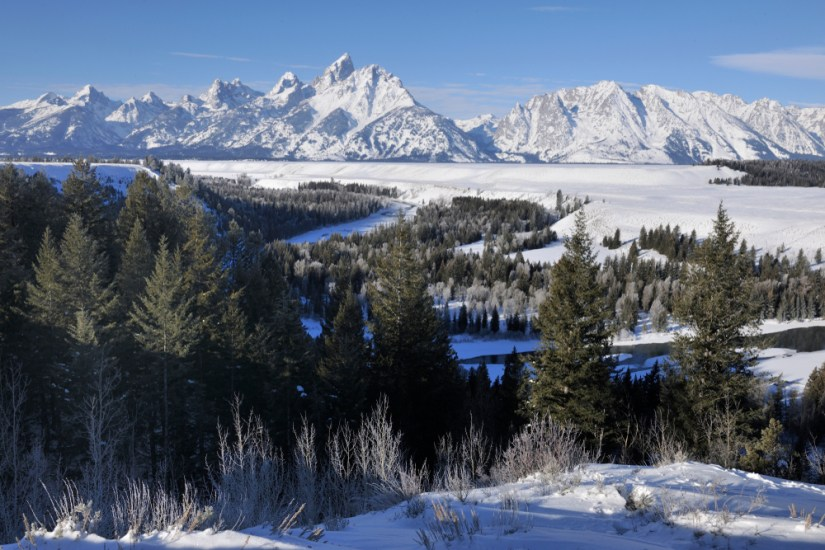 View over a winter Grand Teton landscape with a river, trees, and snow-covered mountains.