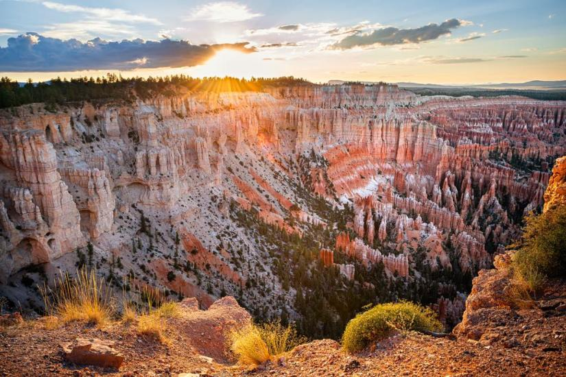 Sun setting over a canyon full of red and white hoodoo landforms.