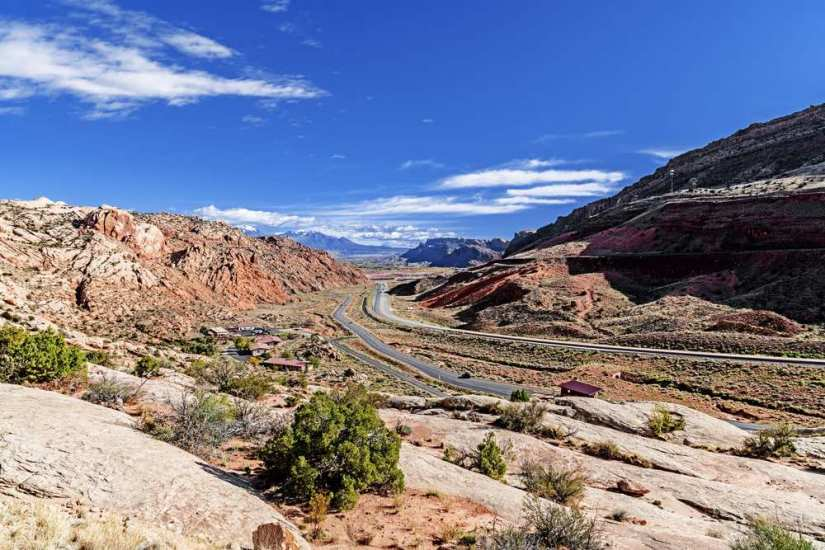 Highway 70 going through Moab with red rocks and desert landscape around it.