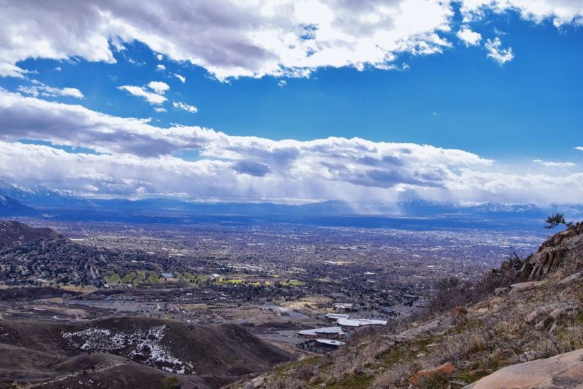 View of Salt Lake City in the far distance from the trail to the Living Room on a partly cloudy day.
