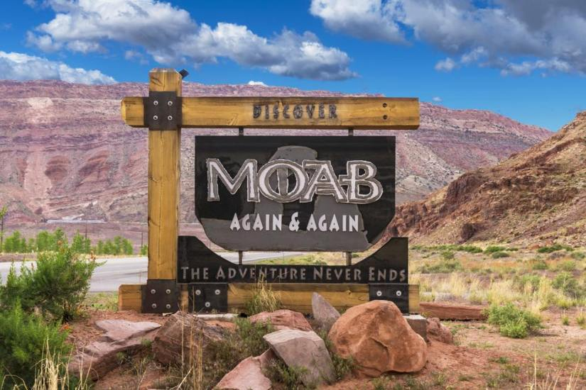 "Sign for the town of Moab which reads ""Moab Again & Again The Adventure Never Ends"" with a desert landscape in a background."