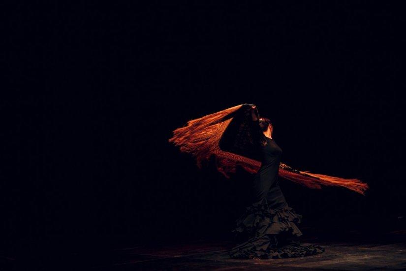 A female flamenco dancer in a dark room swirling her scarf around artistically.