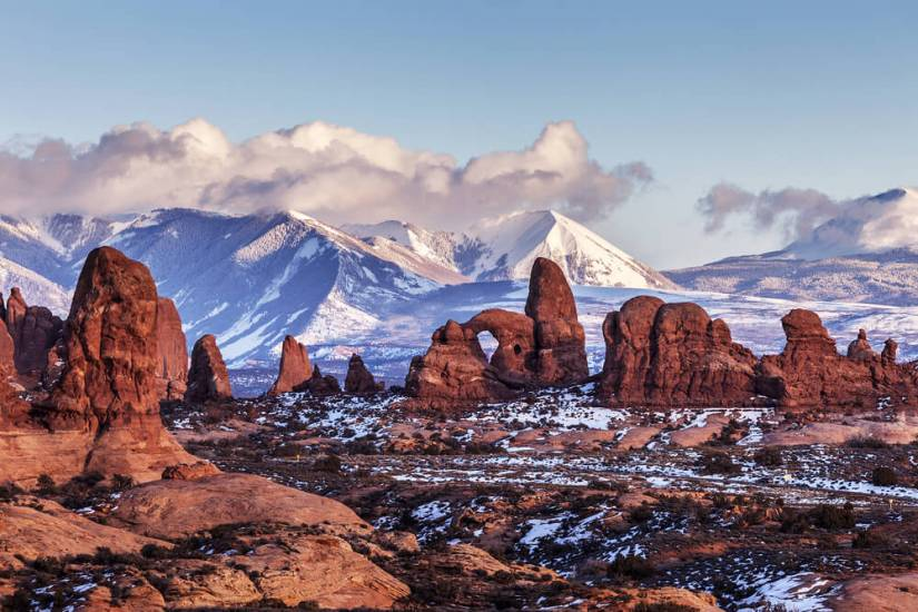 View from afar of the beautiful Turret Arch (which looks like a castle made of natural rock arch) against a backdrop of snow-covered tall mountains, with some light snow on the ground as well.