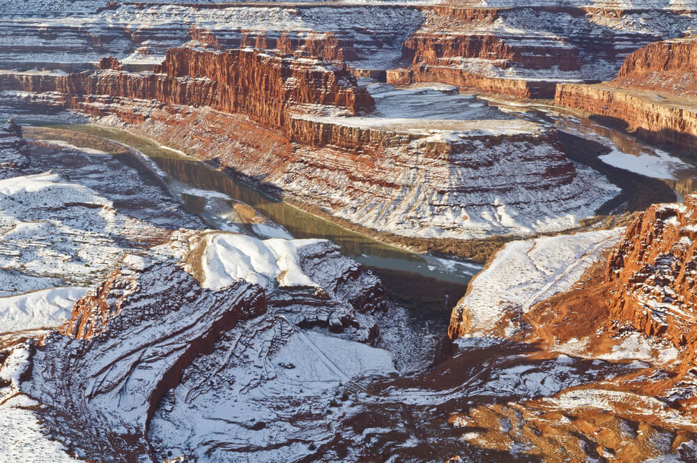 A landscape resembling the Grand Canyon with lots of layered rock carved away by the bend of a river, all the layers of rock are covered in a light snow, alternating orange and white colors.
