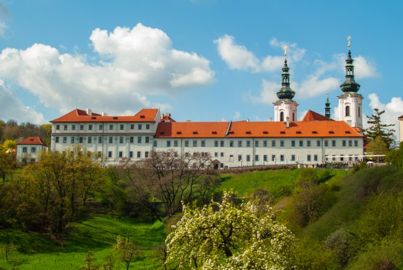 A view from the side of Strahov monastery, a white monastery with a red tiled roof and two towers, on the top of a small hill.