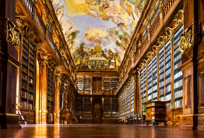An ornate library room with a pastel painted ceiling with lots of detailing and rows upon rows of books with wooden shelves and carved wood detail.