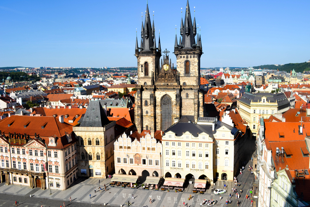 The view of the famous Prague church from a high vantange point, people down in the square looking very small, with lots of red roof architecture and pastel building facades surrounding the church in the middle of the photo.
