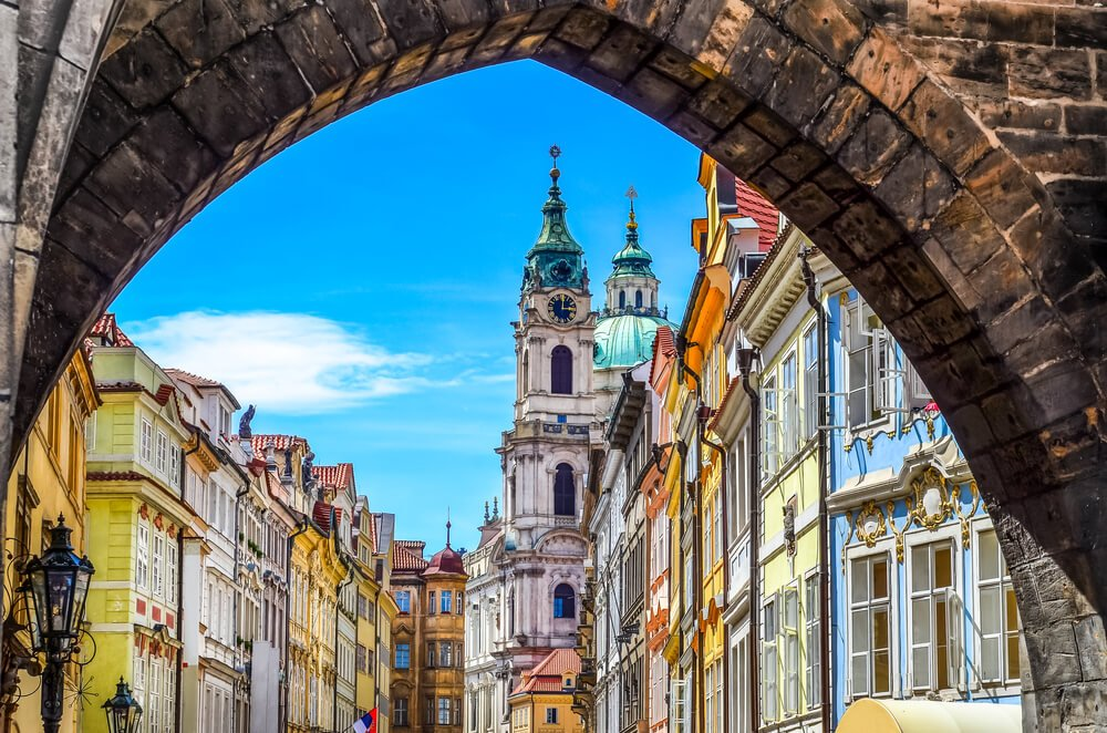 Pastel colored facades in the Old Town as seen through an old stone gate