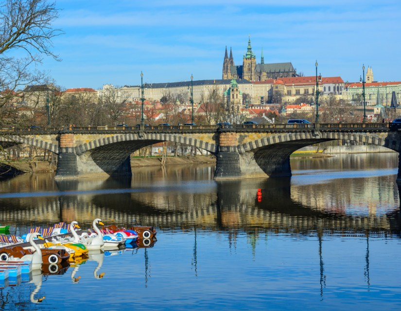 View of Legion Bridge from the water with a view of some novelty water boats (such as swan boats) in the water. Prague Castle is in the background.
