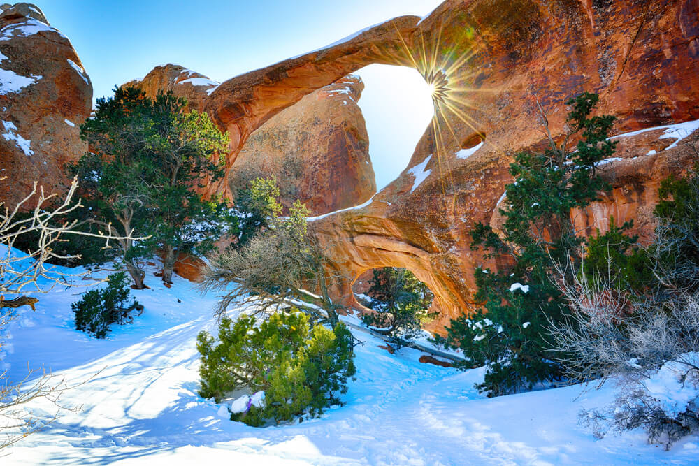 The famous Double O Arch in winter, two arches one on top of the other in the winter snow with a sunburst coming through the top arch.