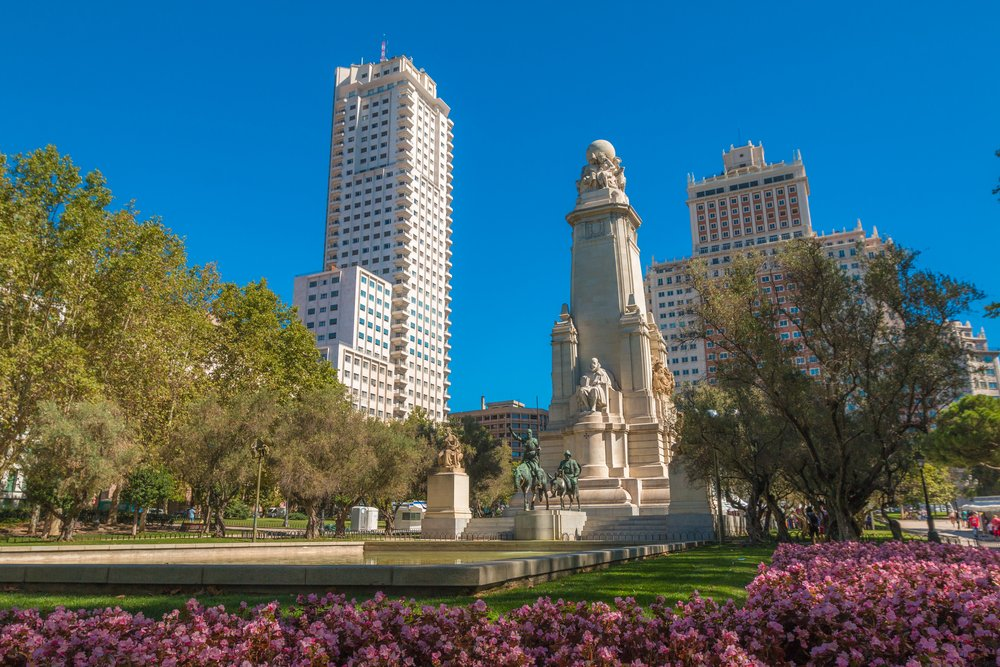 A giant statue in the middle of the park with two skyscrapers around it.
