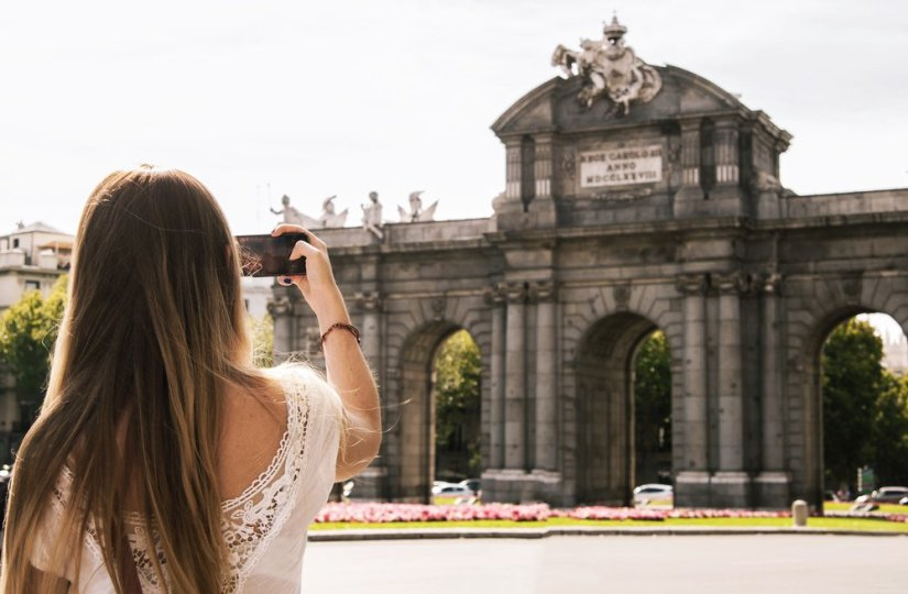 A light-haired woman with a smartphone taking a photo of a famous Madrid landmark.