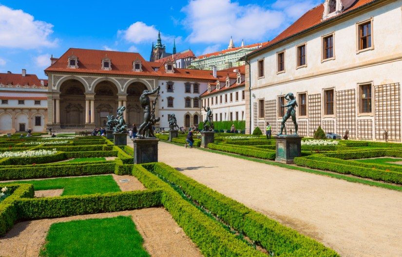 Interior landscaped gardens of the Prague Castle, with statues, green low hedges, buildings with interesting tile work, and red roofed architecture.
