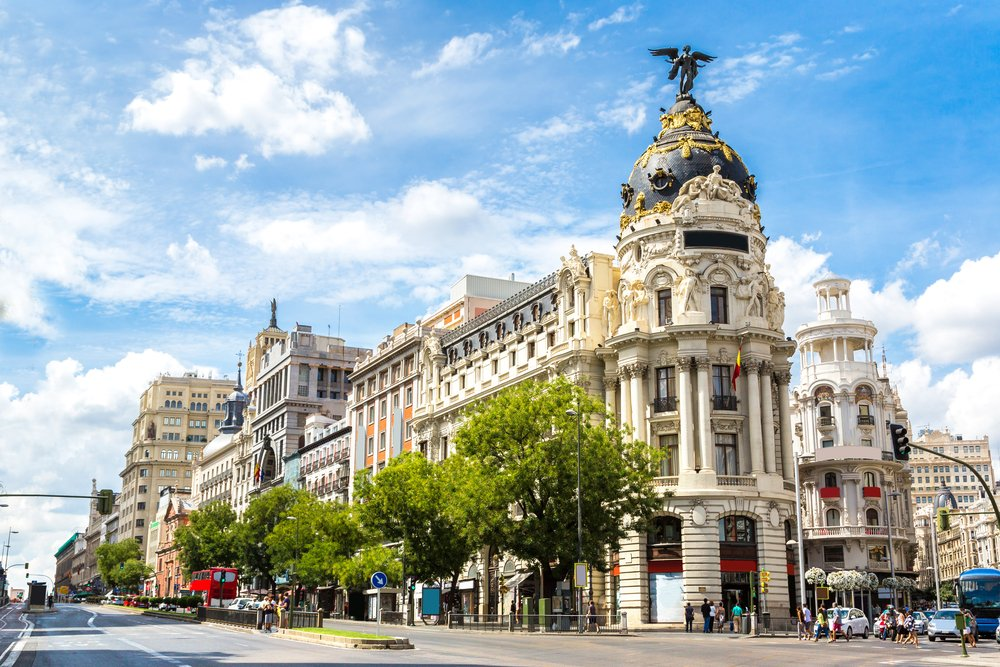 A grand European boulevard with a building with an angel on top of the roof