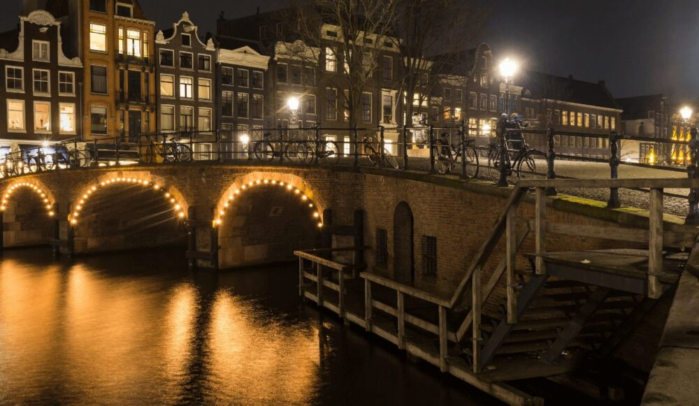 Lights on the canal, with bicycles chained to the bridge, surrounded by traditional canal houses in Amsterdam at night.
