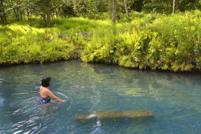 Woman with short brown hair in a colorful bathing suit in turquoise water at a hot spring in Canada surrounded by green grass and trees.