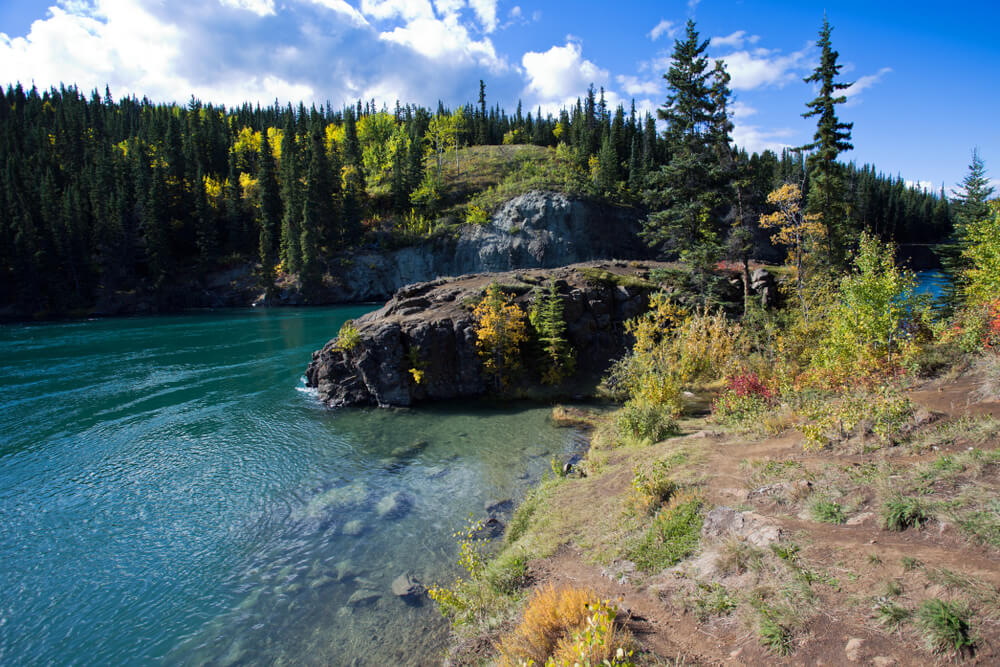 Brilliant turquoise water on the Yukon River, surrounded by rocks and green trees