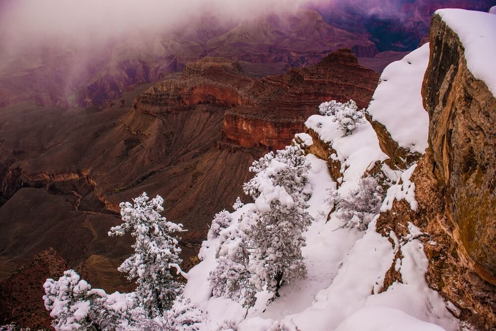 Snow covering red rocks at the Grand Canyon, other parts of the canyon left untouched by snow, as fog rolls on the top of the canyon