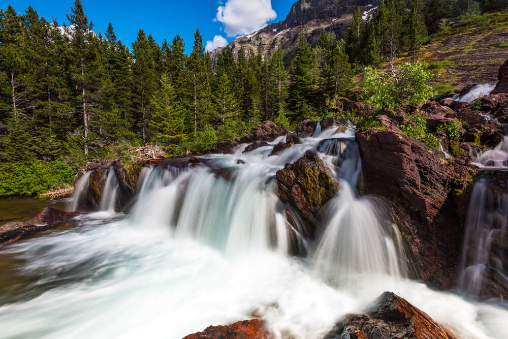 Small cascade over red rocks at Redrock Falls, a popular hike in Glacier National Park, surrounded by trees and blue sky.