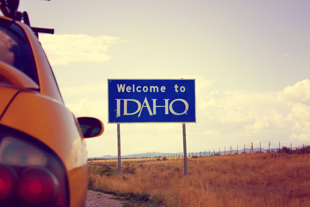 """Sepia-toned photo which shows the back of a car approaching a sign which says """"welcome to Idaho"""" on an Idaho road trip with a field in the background."""