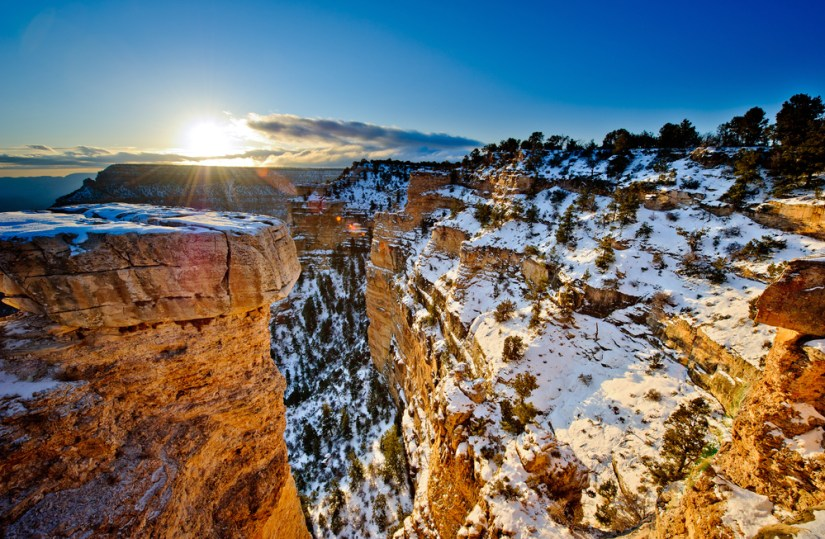 Snow covered landscape at the Grand Canyon in winter, red rocks with patches of white snow with the sun rising above the canyon at sunrise.
