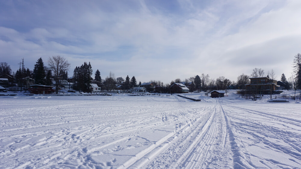 Snowmobile tracks on the frozen lake at Whitefish Lake in Whitefish, MT with houses and lodges in the background.