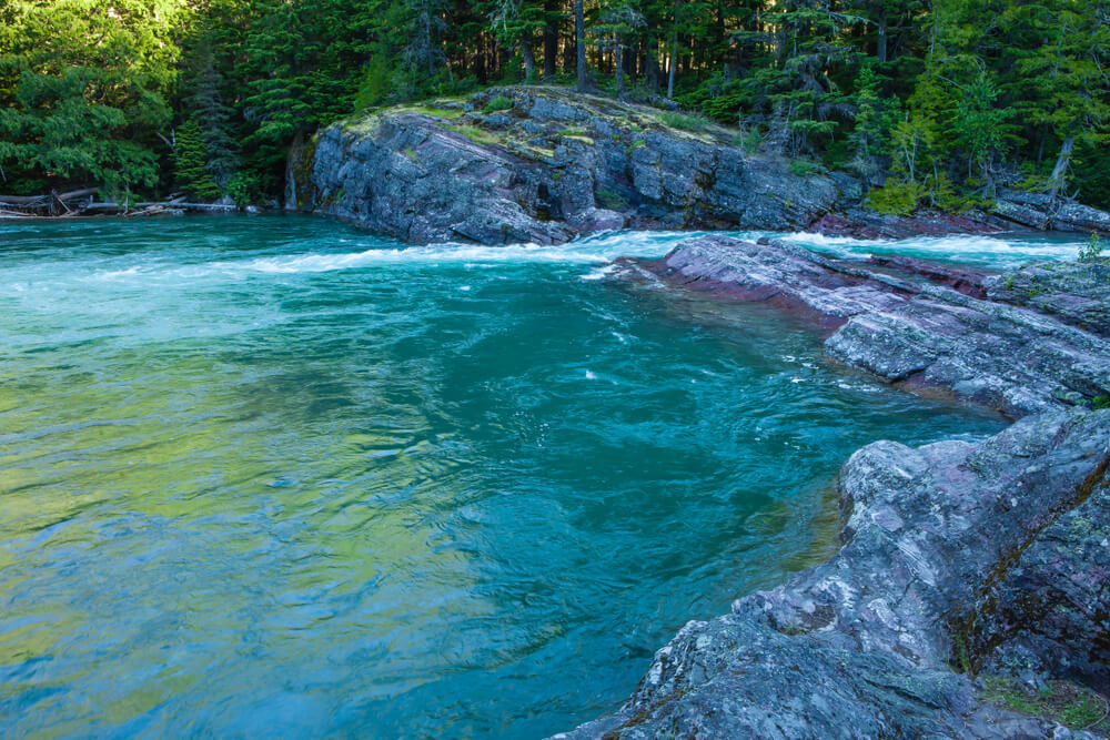 Brilliant emerald-turquoise waters at Upper McDonald Creek, surrounded by rocks covered in green moss and trees.