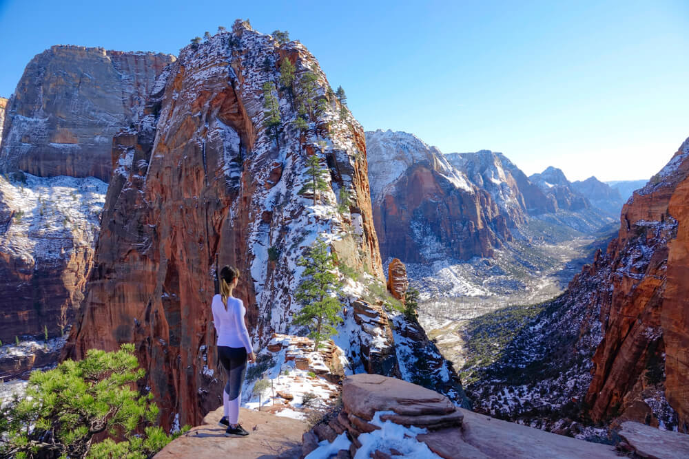 A woman in a lavender top and leggings hiking the ridge of Angel's Landing covered in a light snow, looking over a snow-covered valley in Zion in winter.