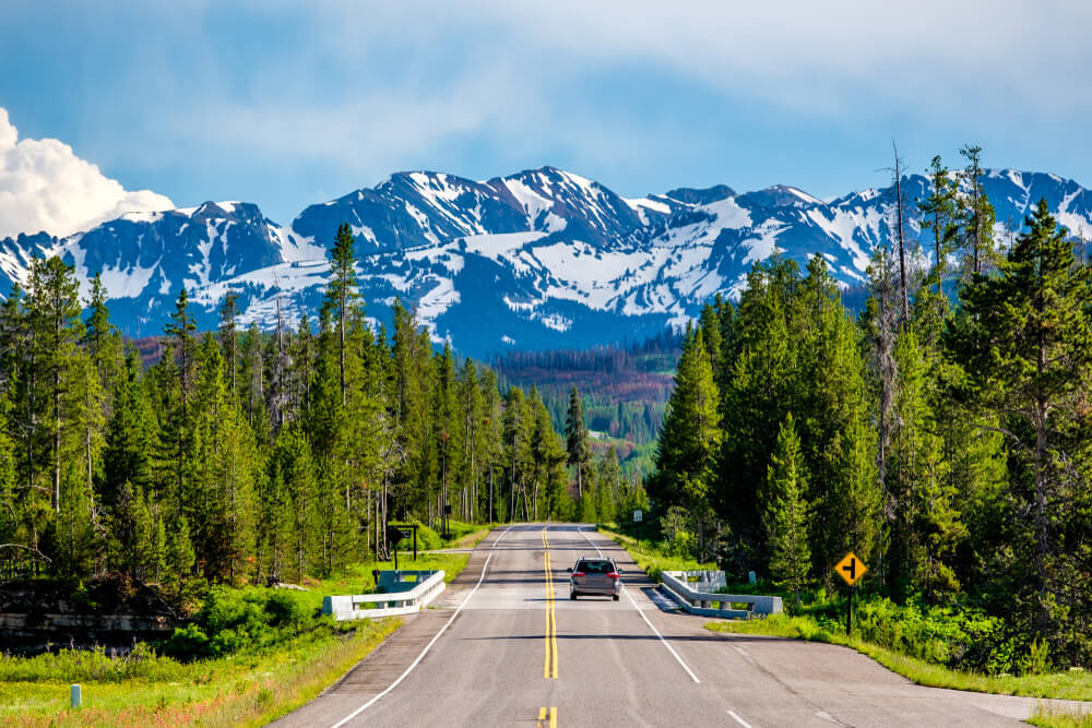A car on the road heading towards snow-covered mountains on a Yellowstone road trip between Yellowstone and Grand Teton National Parks.