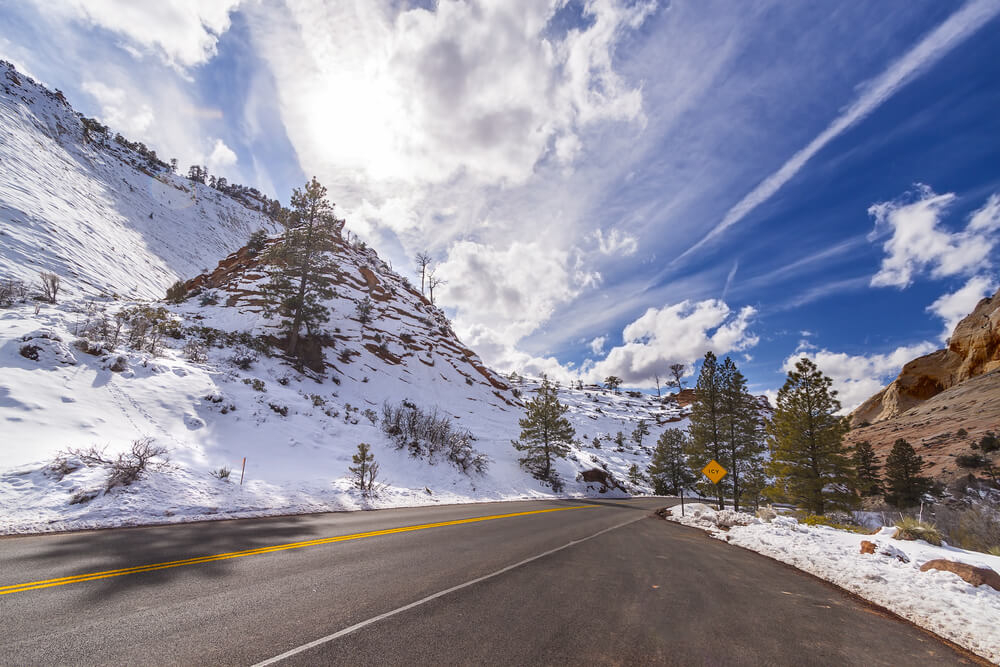 Snow-covered canyon walls with a sunny sky with some clouds, a plowed road that is empty winding through Zion in winter.