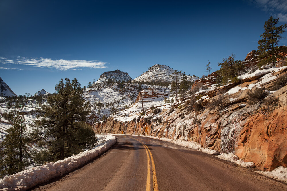 Curve in the road going through a snow covered section of Zion National Park in the winter on a sunny day