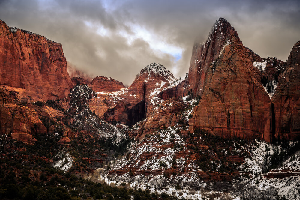 Kolob Canyon walls covered in a light snow which shows from underneath the red rock, a stormy sky with dark clouds above.