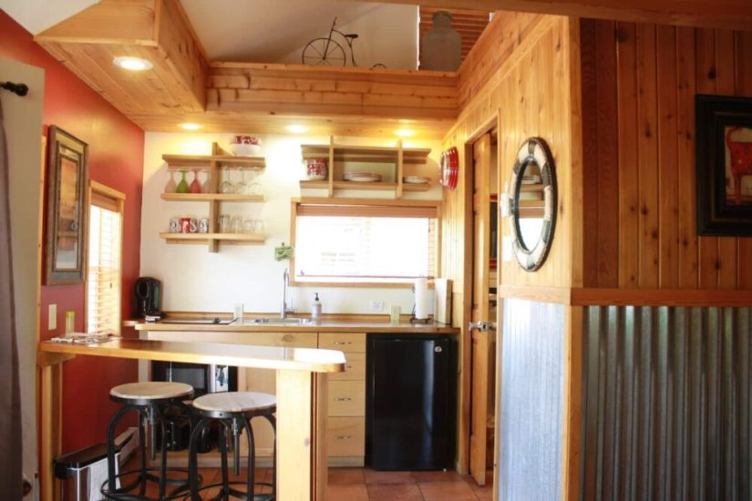 Wooden house with aluminum wall paneling up to halfway up the wall, showing an open layout kitchen with two stools for eating at the bar.