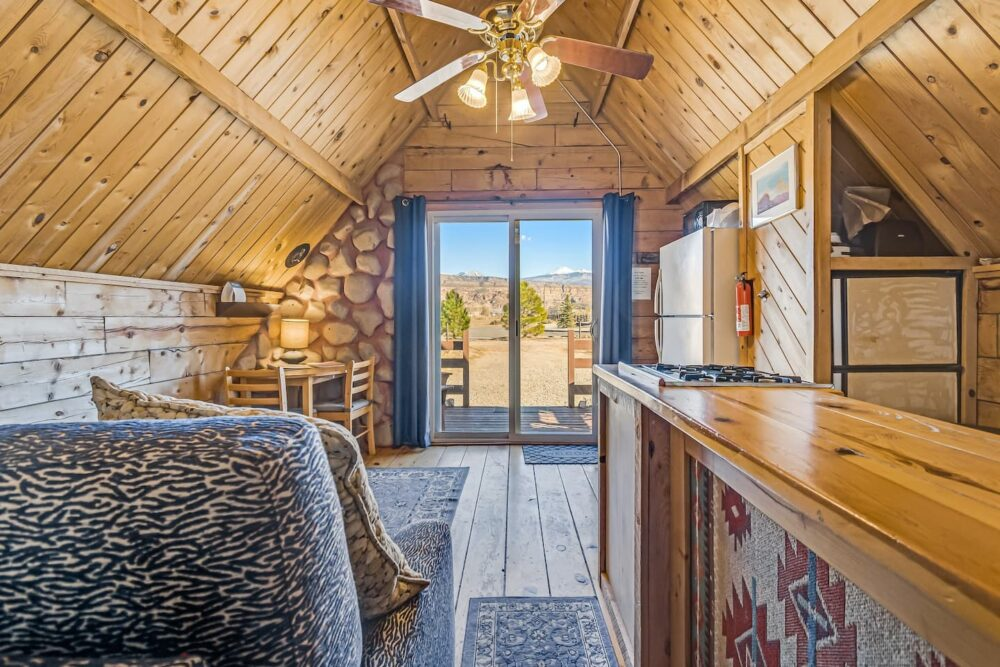 Interior of a rustic A-frame cabin with light wood ceilings, glass doors opening up into the Moab landscape.