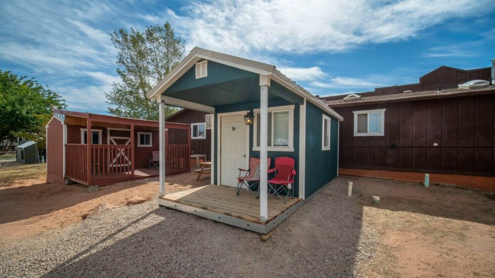 Green tiny house with two camping chairs in front, next to a barn-looking red building in Moab.