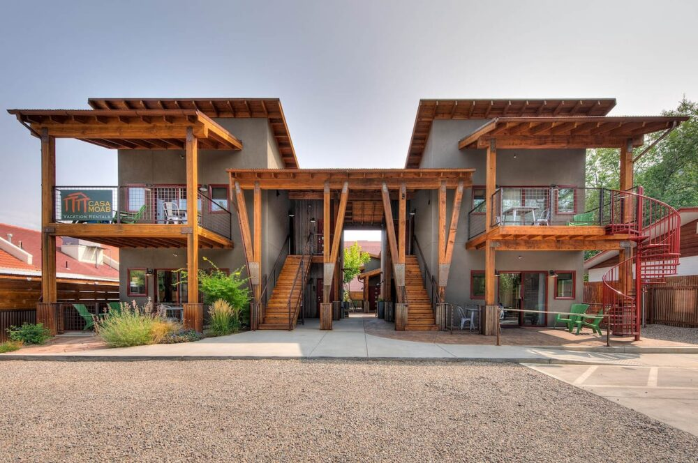 Two gray and wooden houses connected by a roof and twin staircases leading up the upper level, with gravel on the ground in front of the houses, at this popular Airbnb in Moab.