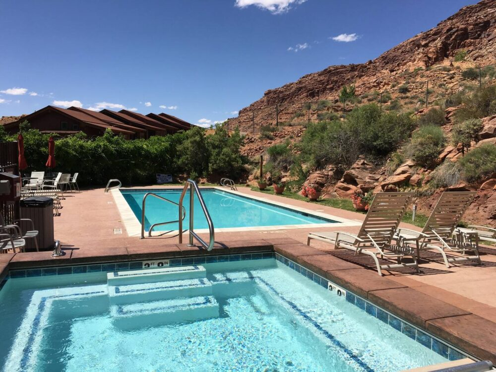 Pool and hot tub near the stunning red rocks of Moab, Utah, with some pool loungers outside.
