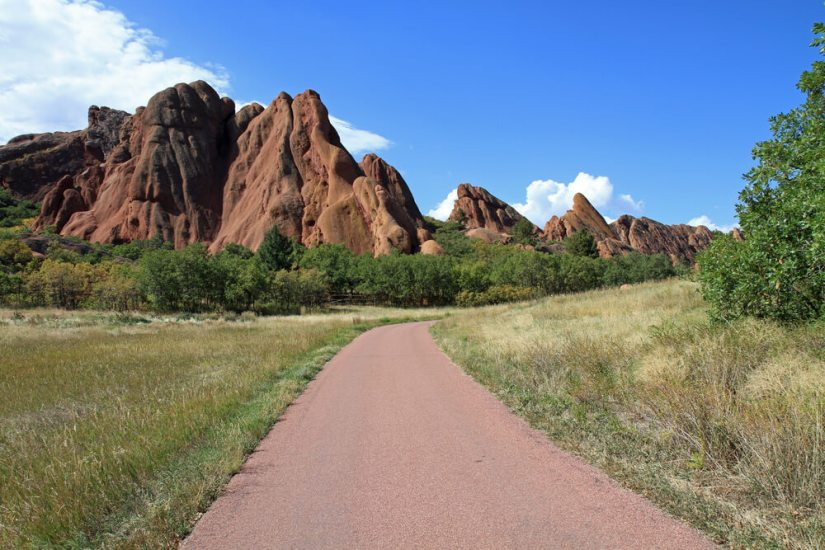 Paved path with sandstone orange rock formations forming peaks in the sky