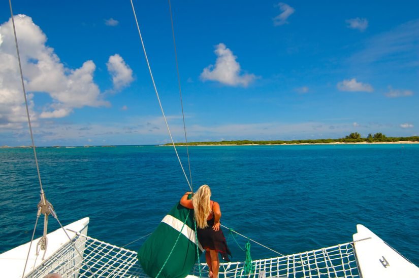 a blonde tan woman in a black dress standing on the net area of a catamaran looking at islands in the distance with blue water around