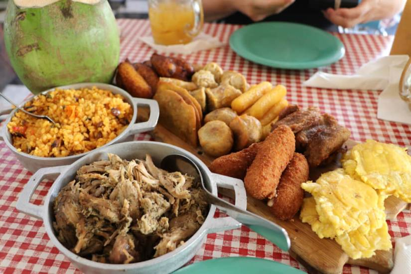 a sampler plate of delicious puerto rican food including fried snacks and pulled pork and rice