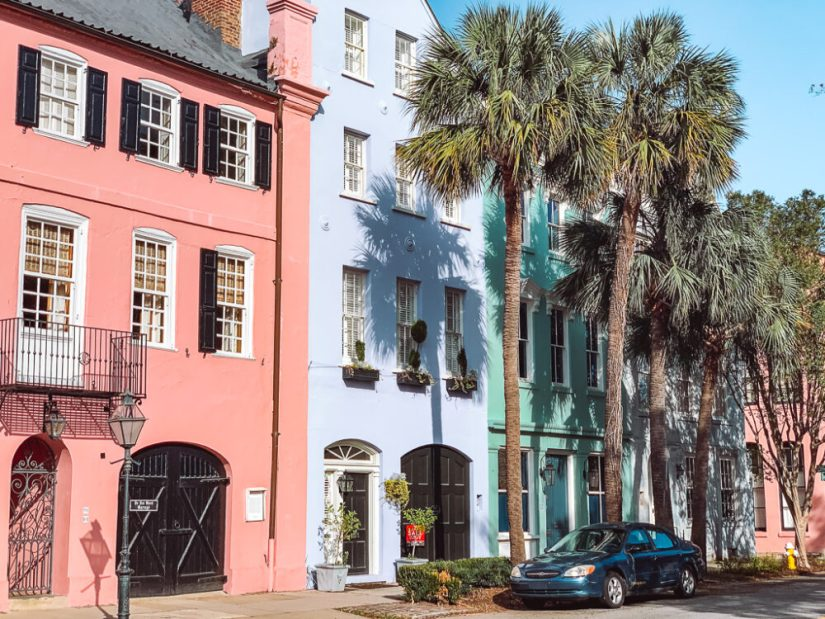 A row of colorful houses -- pink, pale purple and mint green -- on a historic street in Charleston