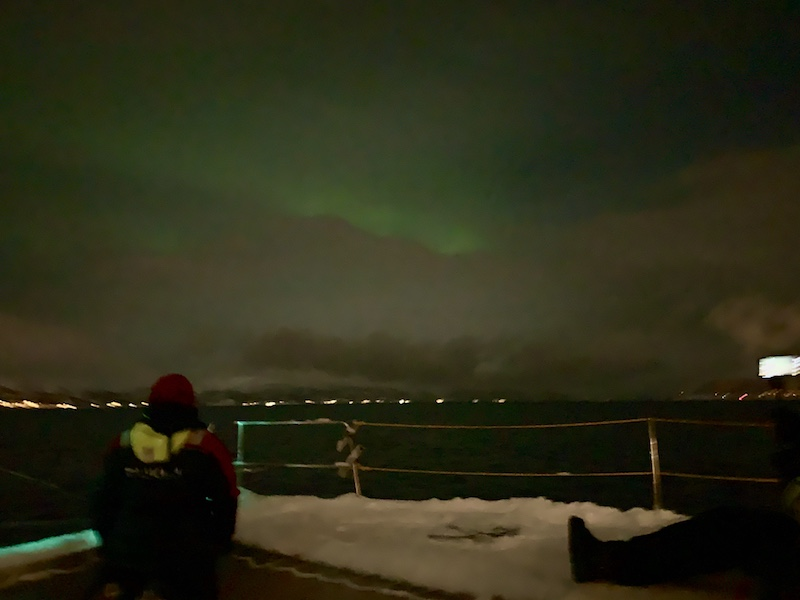 A blurry photo of the Northern lights appearing over the fjord on a sailing cruise near Tromso
