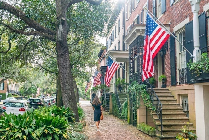 american flags, beautiful brick houses, and oak trees and one woman walking down the street in savannah ga