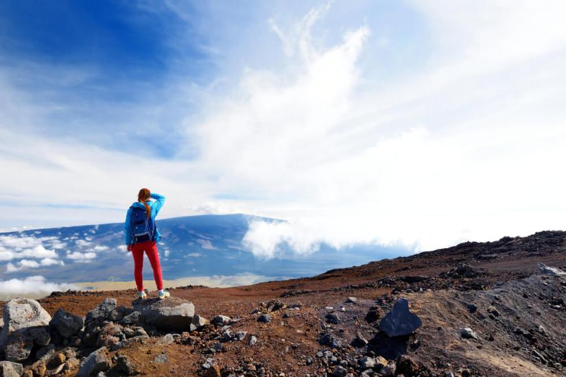 female hiker standing on mauna loa looking at the clouds and views below the summit