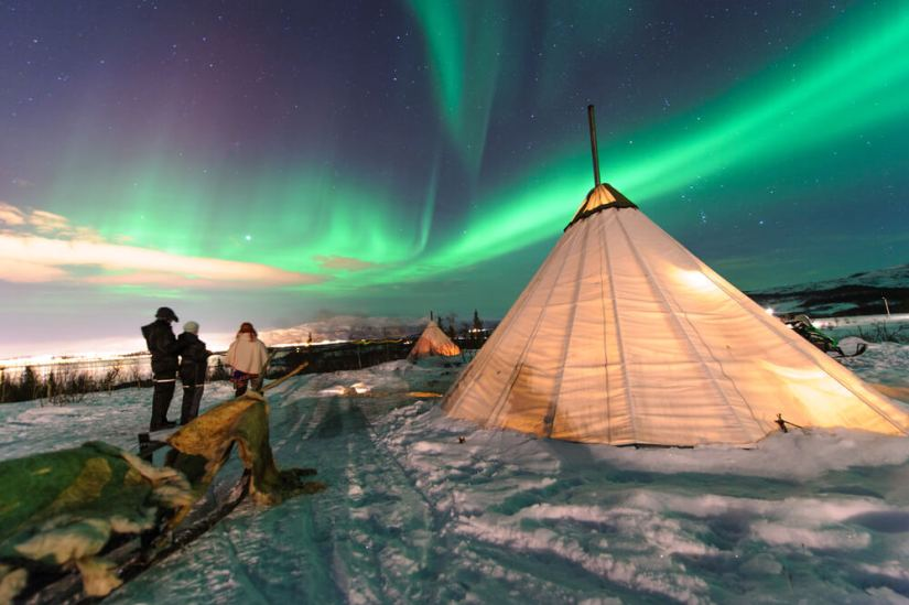 A sami reindeer camp with the aurora over it