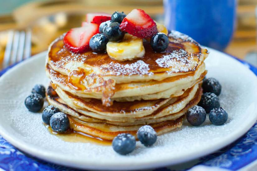 A stack of many pancakes with blueberries, strawberries and bananas.