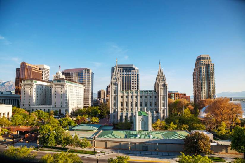 The skyline of Salt Lake City in the afternoon light with autumn trees and green trees