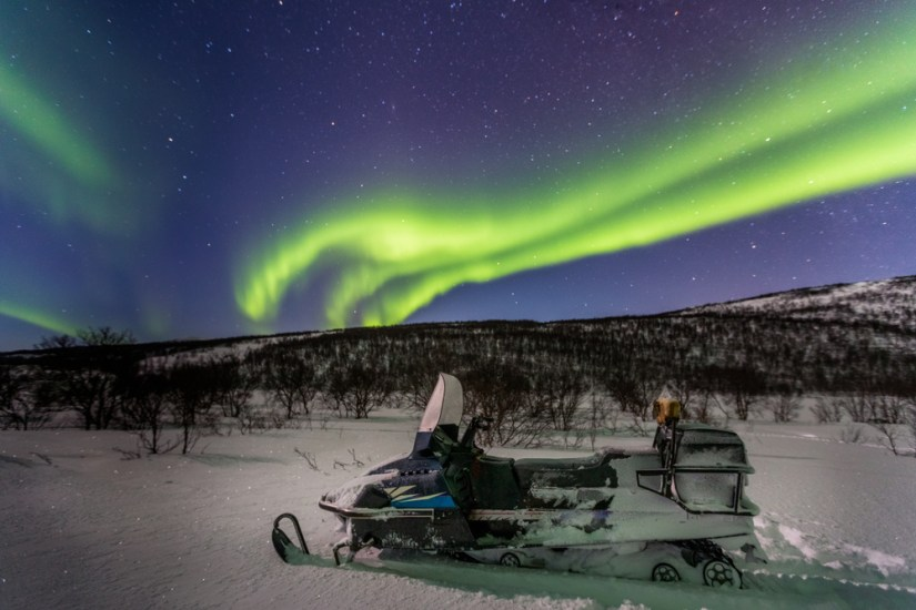 Snowmobile with aurora in the background in Norway